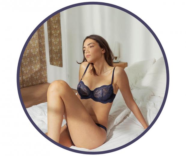Woman sitting on bed wearing blue lace Simone Perele bra