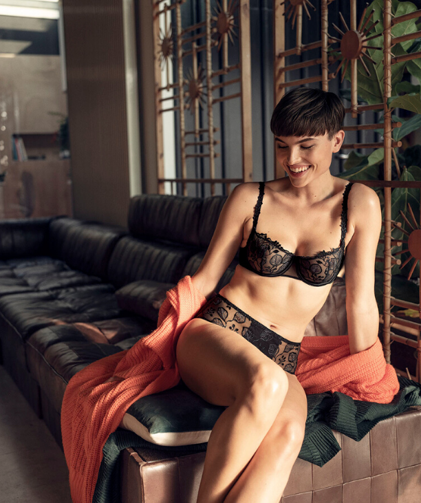 Sarah Connelly Lingerie shop Edinburgh Glasgow: model on sofa wearing Simone Perele Black Half Cup bra and shorty set