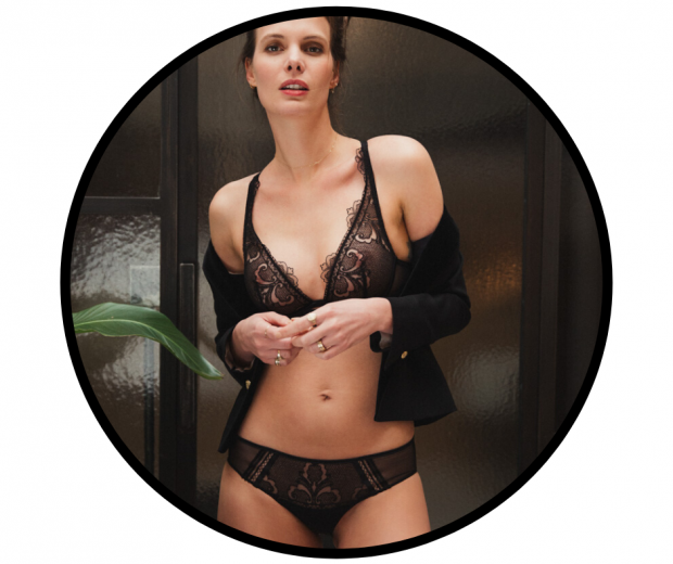 Woman facing camera wearing black lace triangle bralette and tanga with cardigan