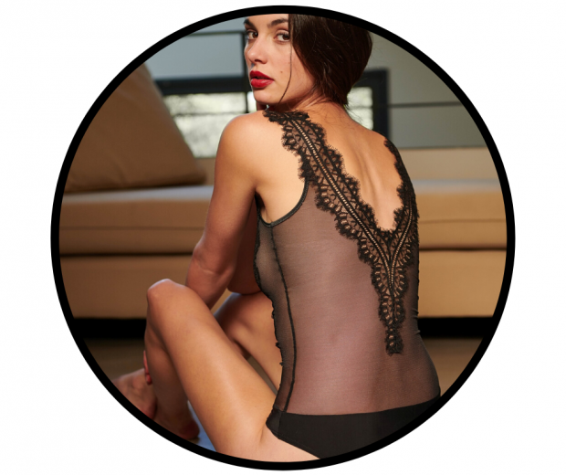 Woman sitting with back to camera wearing black low-back sheer lace body