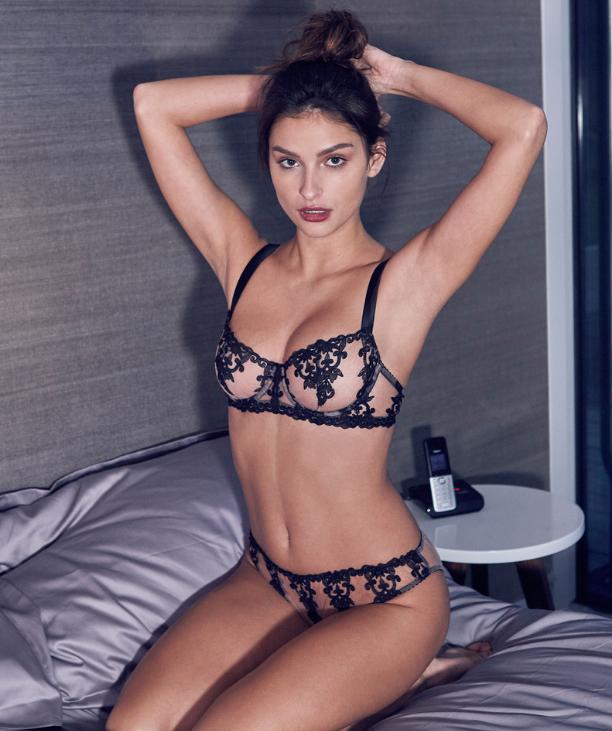 Woman looking confident wearing black sheer balcony bra